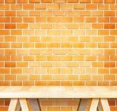 Table moderne en bois vide et mur de briques orange grunge dans le backgrou image libre de droits