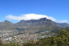 Table Mountain. A view of Table Mountain with the buildings at it's feet and a cloth of a cloud over the top of the mountain taken from Signal Hill in Cape Town Stock Photography