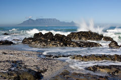 Table Mountain. From Bloubergstrand with rocks in the foreground and water splash Stock Images