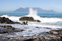 Table Mountain. From Bloubergstrand with rocks in the foreground and water splash Royalty Free Stock Image