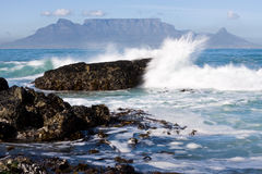 Table Mountain. From Bloubergstrand with rocks in the foreground and water splash Stock Photo