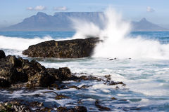 Table Mountain. From Bloubergstrand with rocks in the foreground and water splash Royalty Free Stock Images