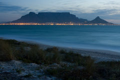 Table Mountain. From Milnerton beach with grass in the foreground at night Stock Images