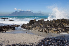 Table Mountain. From Bloubergstrand with rocks in the foreground and water splash Royalty Free Stock Photo