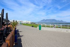 Table Mountain. Beautiful landscape view of famous wonder of the world table mountain against a blue sky with sea ocean and cafe tables in the foreground from Royalty Free Stock Images