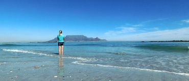 Table Mountain from Blue Berg Beach. A landscape view of Table Mountain as seen from Blue Berg Beach. Blue sea and shore in foreground, three silver gulls and Royalty Free Stock Image