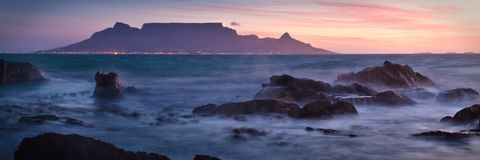 Table Mountain at dawn. Vista of Table Mountain at dawn as seen from Bloubergstrand Stock Images