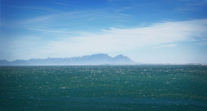Table Mountain from Gordons Bay. The rear view of Table Mountain from the Indian Ocean side, at Gordons Bay. Wind whipped waters Stock Photo