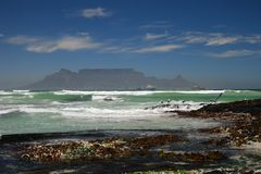 Table mountain growing up out of the Atlantic ocean royalty free stock photos