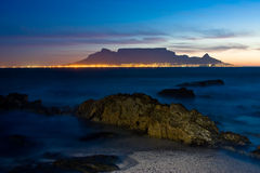 Table mountain sunset. Sunset over Table Mountain with crocodile looking rock in foreground and city skyline Stock Image