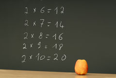 Table multiplication on blackboard desk with apple Royalty Free Stock Images