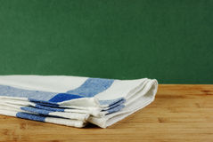 Table-napkin and old wooden deck table with green grunge backgro Stock Photo