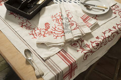 Table Napkins of Various Designs on Tablecloth of Various Design. An assortment of folded table napkins of differing printed patterned design placed atop of Royalty Free Stock Photos