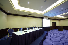 Table near screen in conference hall Royalty Free Stock Photos