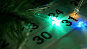 On the table is the New Year`s December calendar and the New Year lights are burning around the date of December 31. Close-up, the new year 2019, calendar stock footage