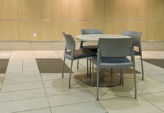 Table Next To Wall. A small table with four chairs in a cafeteria or business centre Royalty Free Stock Image