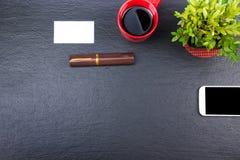 Table noire de bureau avec l'ordinateur, le stylo et une tasse de café, sort de choses Vue supérieure avec l'espace de copie Images stock
