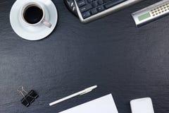 Table noire de bureau avec l'ordinateur, le stylo et une tasse de café, sort de choses Vue supérieure avec l'espace de copie Image stock