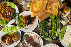 Table with normal food, steaks and potatoes. Royalty Free Stock Photos