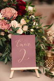 Table number and flower composition. Table number and bouquet of red white and pink roses composition Royalty Free Stock Photos