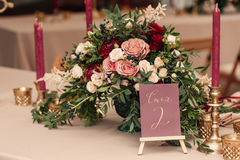 Table number and flower composition. With candles on candlestic Royalty Free Stock Images