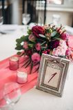 Table number in silver frame with a numeral one. Burgundy bouquet on background Royalty Free Stock Image