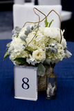 Table Number 8. With white flower centerpiece stock photo
