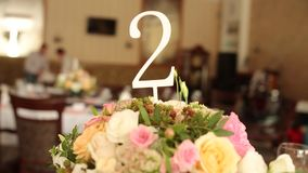 Table numbers at restaurant interior decoration for wedding or birthday with white and blue colors. Holiday floristics stock video footage