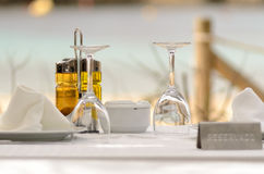 Table with oil, some glasses and a reserved sign. This picture shows a table in a beach restaurant with oil, some glasses and a reserved sign on it Royalty Free Stock Images