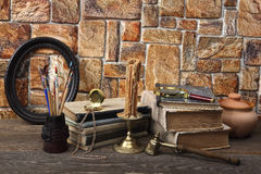 On the table are: old books, a wax candle in a bronze candlestick, a ceramic pot, a pocket watch, tassels in a carved glass and a Royalty Free Stock Image