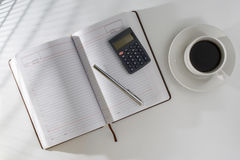 On the table in an open diary and a pen with a calculator, standing next to a cup of coffee. The table at the window, the light on the table through the blinds Royalty Free Stock Photos