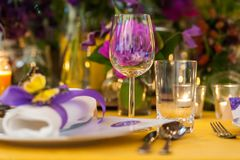 Table ornament with glass, plate and flowers stock image