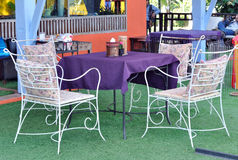 Table in an outdoor porch with cozy chairs Stock Photos
