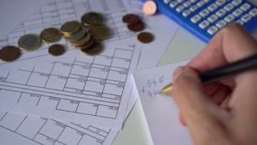 Man`s hand counts expenses in a notebook. On a table with papers, financial bills, a calculator. Man`s hand counts expenses in a notebook stock video
