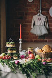 A table for a party served with candles, cakes, bread and fruits on the background of a brick wall stock photos