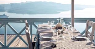 Table on patio, Thira, Santorini Island, Greece. Table on patio overlooking waterfront of Thira on Santorini Island, Greece on sunny day royalty free stock photo