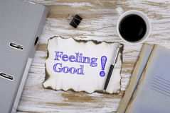On the table a piece of paper and text. Feeling Good! Stock Image