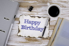 On the table a piece of paper and text - Happy Birthday Stock Images