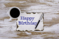 On the table a piece of paper and text - Happy Birthday Royalty Free Stock Photos