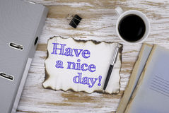 On the table a piece of paper and text. Have a nice day! royalty free stock image
