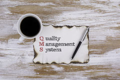 On the table a piece of paper and text. QMS concept: quality man Royalty Free Stock Photography