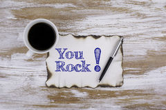 On the table a piece of paper and text - You rock! Stock Image