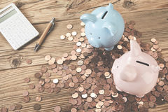Table with piggy banks. Table with two piggy banks standing among pile of coins, calculator and pen Stock Image