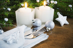 Table Place Setting for Christmas Eve. Winter Holidays. Christmas background. Cutlery on napkin, candles and fir branches on rustic wooden background Stock Image