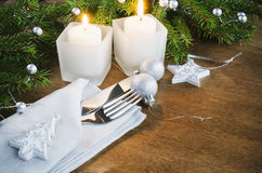 Table Place Setting for Christmas Eve. Winter Holidays. Christmas background. Cutlery on napkin, candles and fir branches on rustic wooden background Royalty Free Stock Photo