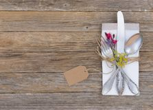 Table place setting with silver cutlery, napkin, flowers and empty name tag. Elegant table place setting with old silver cutlery, fabric napkin, summer flowers Stock Image