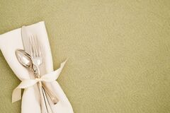 Table Place Setting with Silverware and White cloth napkin on Light Olive Green Brocade Tablecloth as the background with copy spa