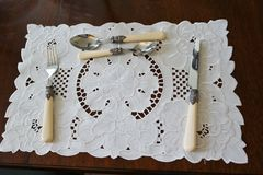 Table place setting. White patterned lace table setting with bone handled cutlery knife fork spoons Stock Images