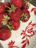 On the table in a plate is a fresh red strawberry. Royalty Free Stock Photos