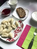 On the table is a plate with lazy dumplings, from which the steam rises. Added sour cream and jam. On the table is a plate with lazy dumplings, from which the stock photo